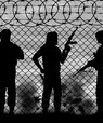 Barbed wire and the silhouette of men with guns in military clothes