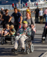 People of all ages walking on a bridge together. Two elderly people on wheelchairs.